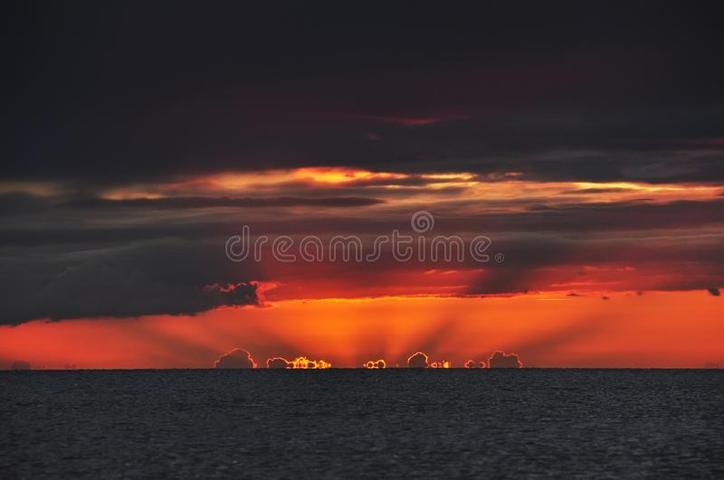 Beautiful dramatic sunset over the sea. Clouds of water on the horizon illuminated by the setting sun. Dark photo. royalty free stock image