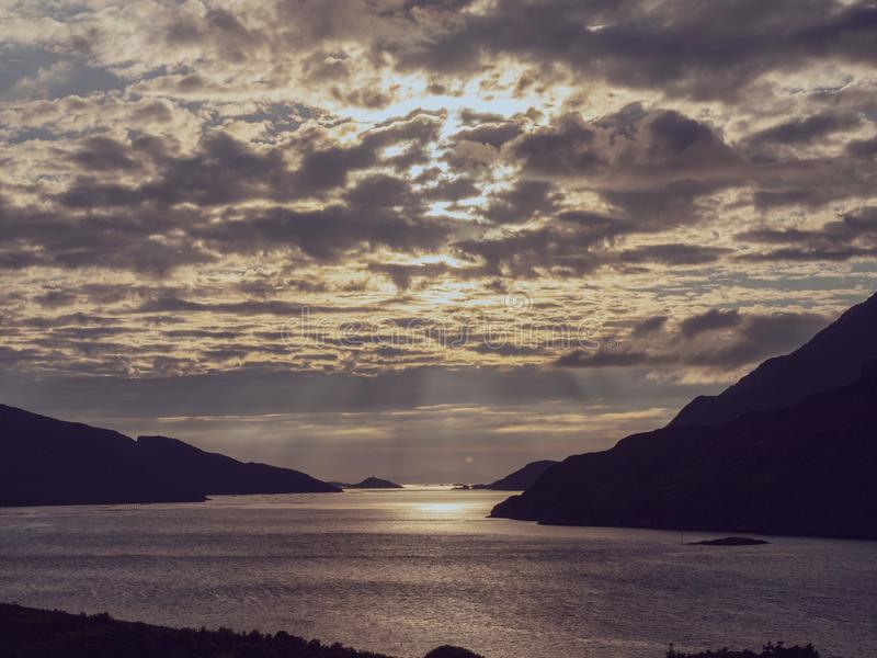 Beautiful, dramatic sunset sky over Killary fjord, county Galway. Sun rays shine through the clouds. Calm and peaceful mood. Toned royalty free stock photography