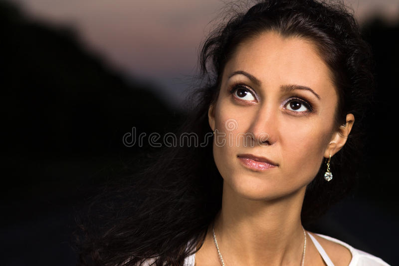 Beautiful dreaming girl at outdoor in the evening. Caucasian young woman on dark background with copy space aside stock photo