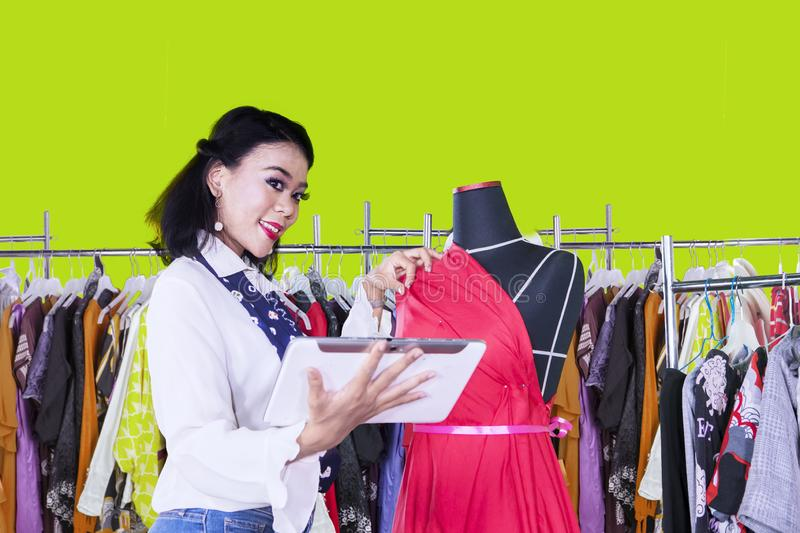 Beautiful dressmaker working with tablet on studio stock image
