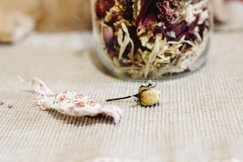 Beautiful dried flowers, different flavors, in glass jar on rust stock photos