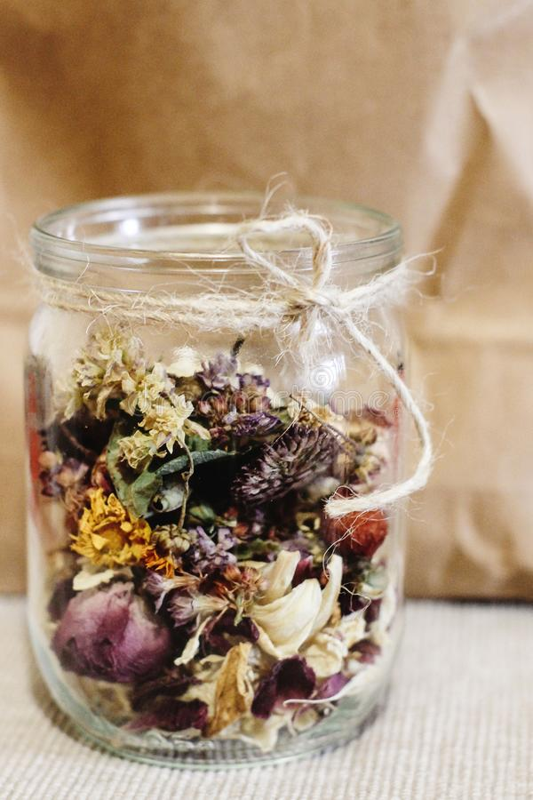 Beautiful dried flowers, different flavors, in glass jar on rust royalty free stock image