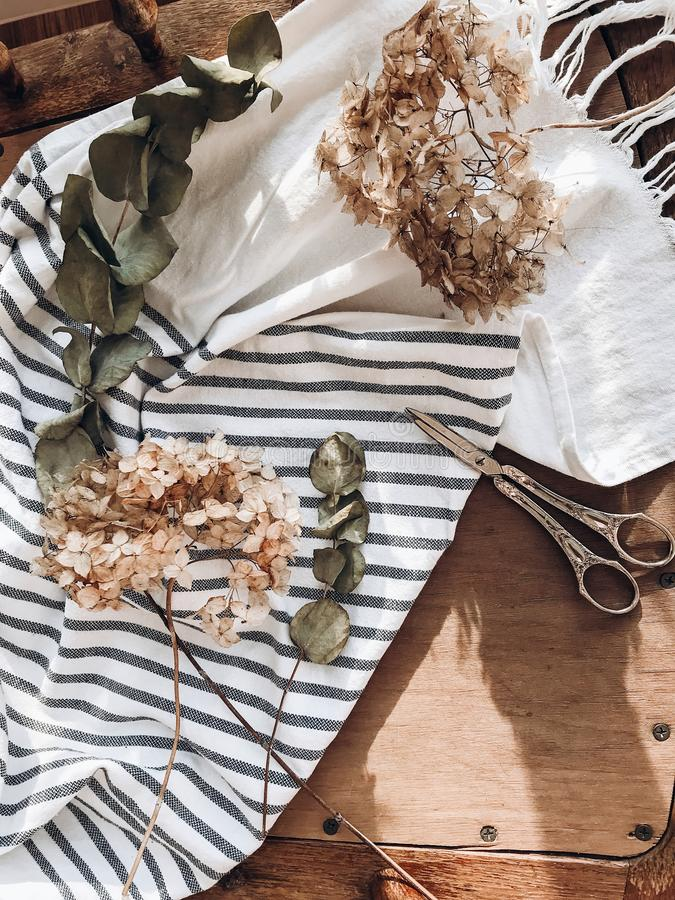 Beautiful dried hydrangea, eucalyptus, scissors and linen fabric on rustic wooden chair, rural still life flat lay. Phone photo stock photos