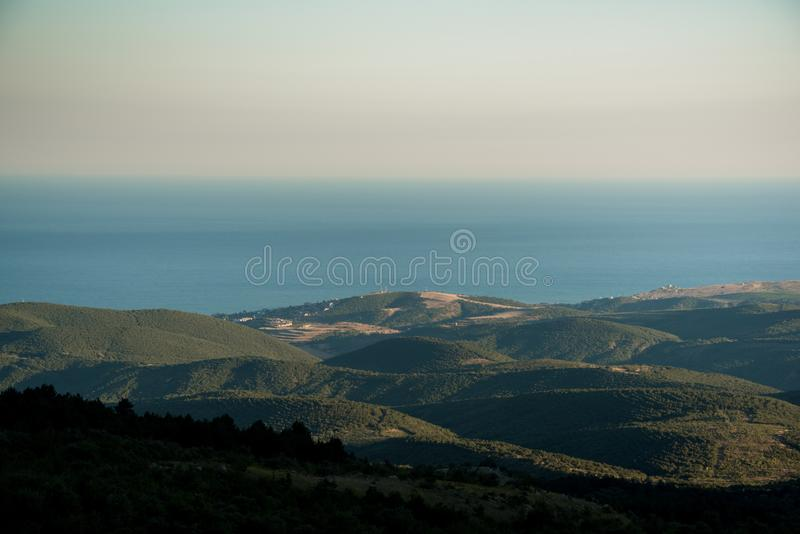 Sunrise over hills and sea royalty free stock photography