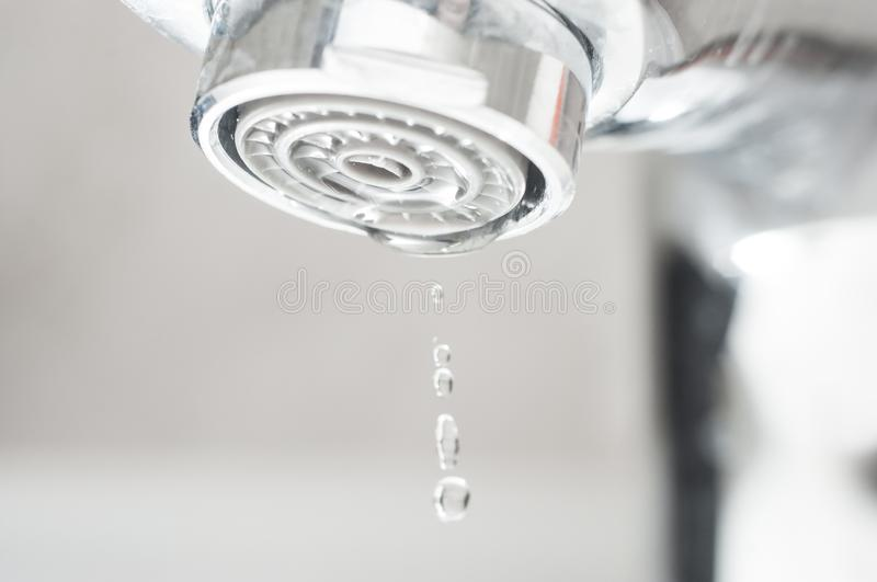 A beautiful drop of water frozen closeup drops from the tap royalty free stock photography