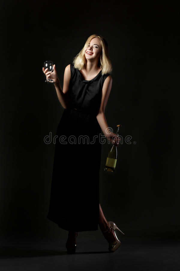 Beautiful drunk blonde woman holding white wine bottle on black background. Party and holiday stock images