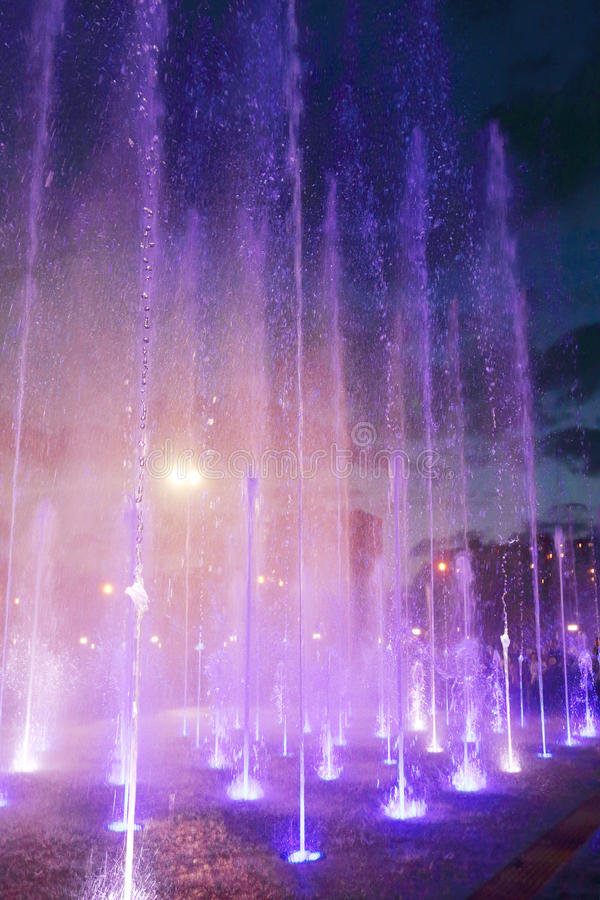 Beautiful dry fountain with bright illuminated splashes stock images