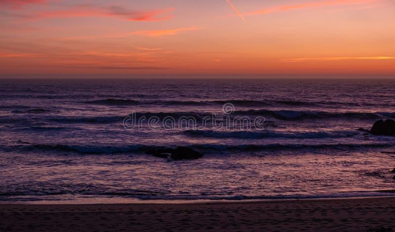 Beautiful dusk over ocean with dark purple waves and orange red sky. Beautiful dusk over ocean with dark purple waves and orange red gradient sky royalty free stock photos