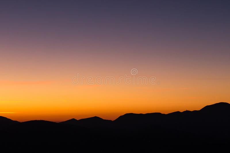 Beautiful dusk over profiles of mountains with orange and purple. Tones, and a lot of copy space stock photos
