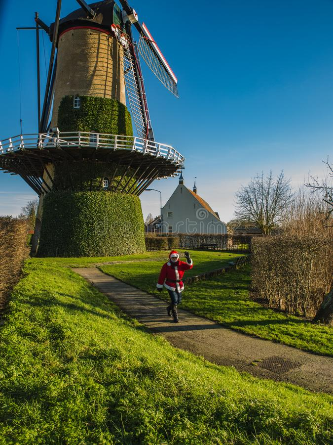 Beautiful Dutch mill and modern Santa Claus on the foreground royalty free stock photo