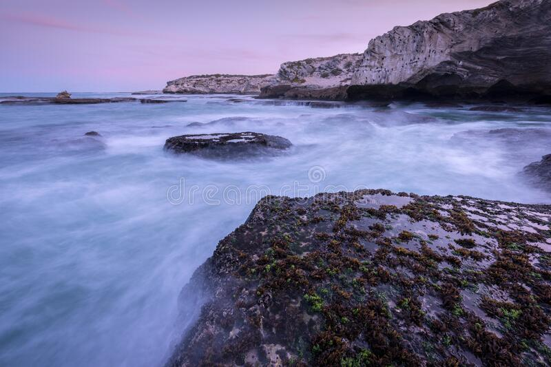 A beautiful early evening seascape with dramatic rocks and misty waves. In the foreground, and a pink sky, photographed on a stormy day after sunset in Arniston royalty free stock photo