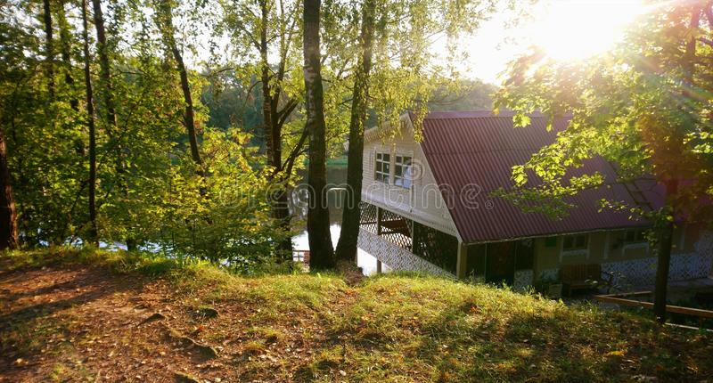 Wooden house in the countryside with trees and river in the background royalty free stock image