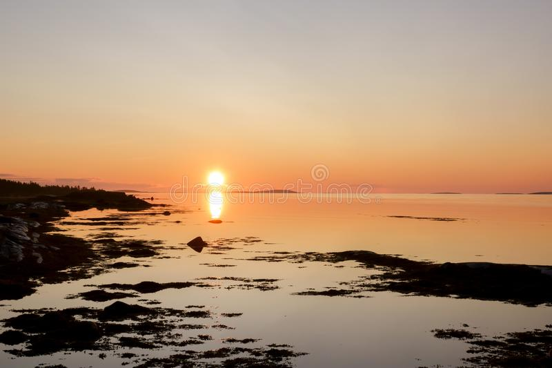 Beautiful early morning sunrise landscape of white sea water dramatic sunrise with first sunlight rays stock image