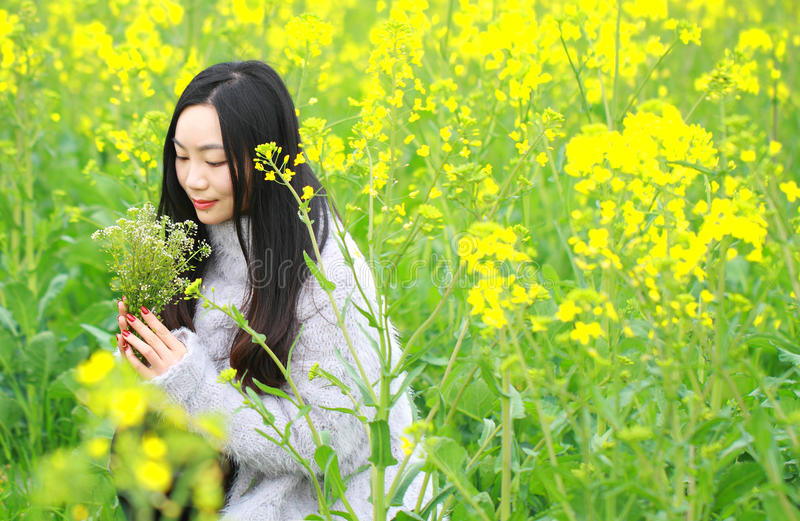 At beautiful early spring, a young woman stand in the middle of yellow flowers filed which is the biggest in Shanghai. A young woman stand in the middle of stock photo