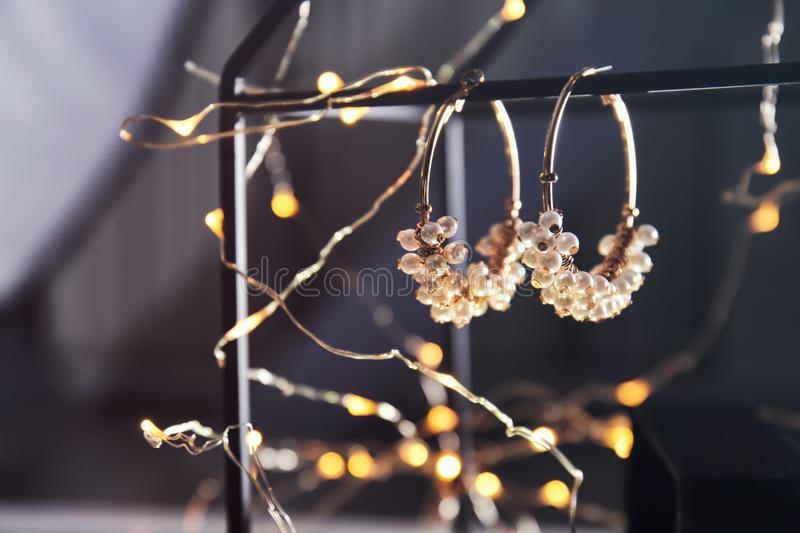 Beautiful earrings and glowing fairy lights,. Closeup royalty free stock photos