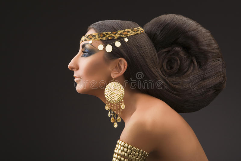 Beautiful east woman. Portrait of the young woman in a profile in east style with a beautiful hairdress and gold ornaments on a black background