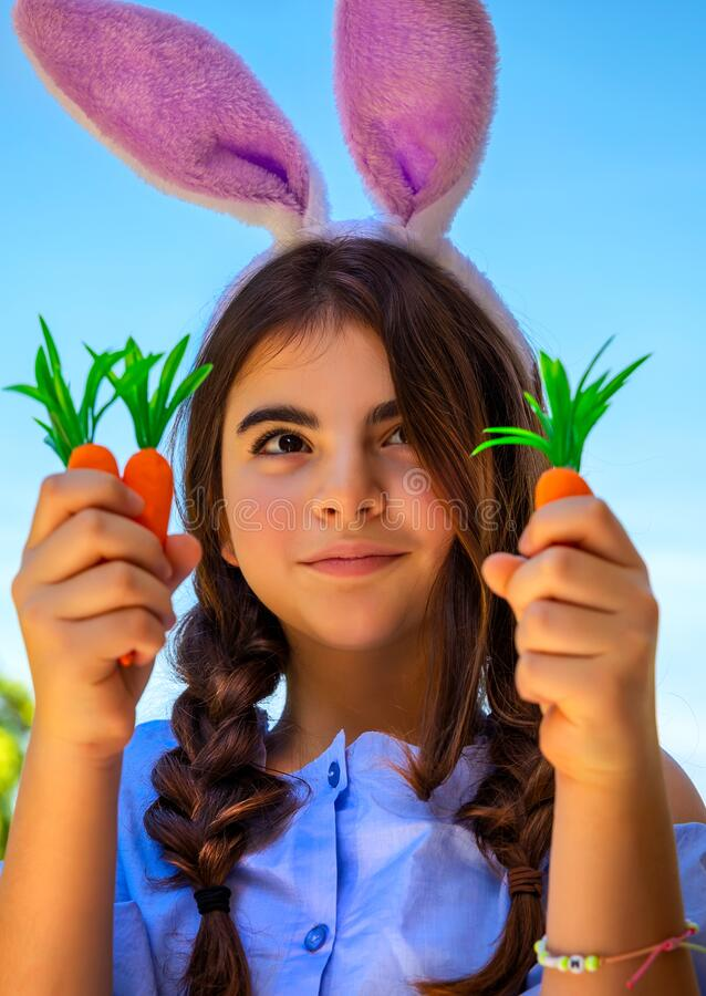 Beautiful Easter bunny girl. Portrait of a cute pre-teen girl celebrating happy Christian holiday, dressed as a an Easter bunny holding carrots, gardening in the stock photo