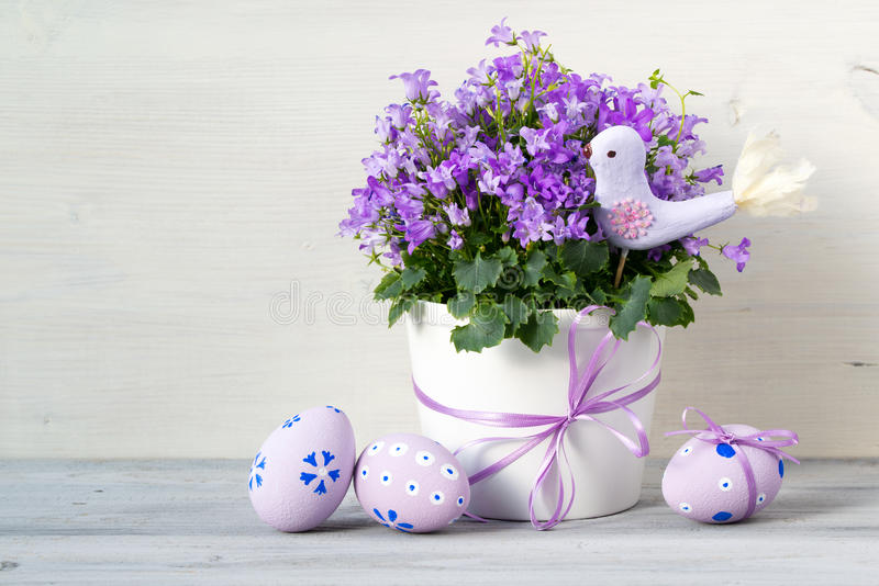 Beautiful easter composition in pastel colors with Campanula flowers, Easter eggs and ceramic bird stock images