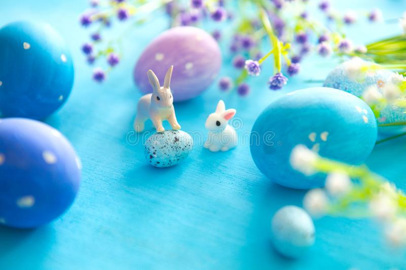 Beautiful Easter eggs with rabbits toy and flowers on blue wooden background, closeup. Easter holiday concept royalty free stock photo