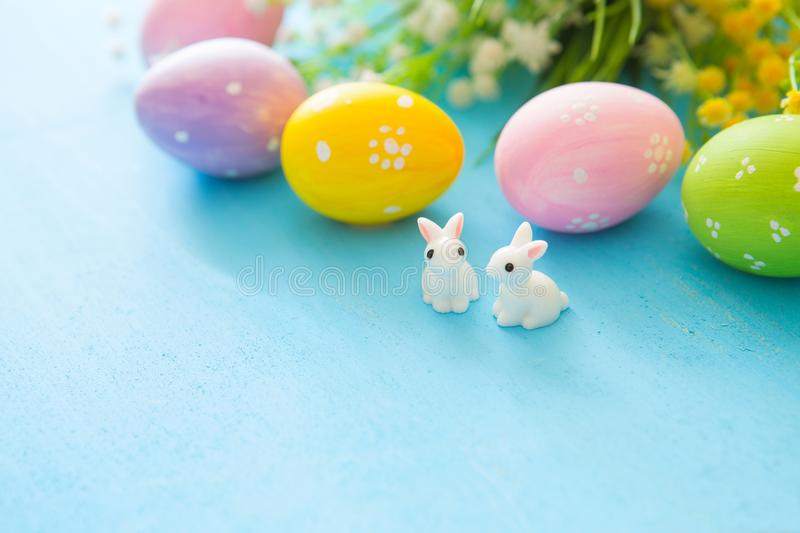 Beautiful Easter eggs with rabbits toy and flowers on blue wooden background, closeup. Easter holiday concept royalty free stock images
