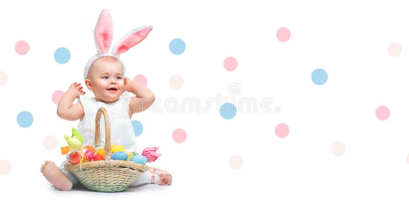 Beautiful Easter smiling little girl wearing bunny rabbit ears, with a basket full of colorful painted Easter eggs royalty free stock photo