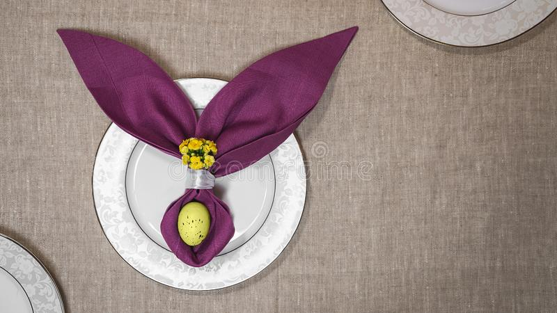 Beautiful Easter table setting with egg, purple napkin Easter Bunny on white plates and on natural tablecloth background. Flat lay, top view stock photo