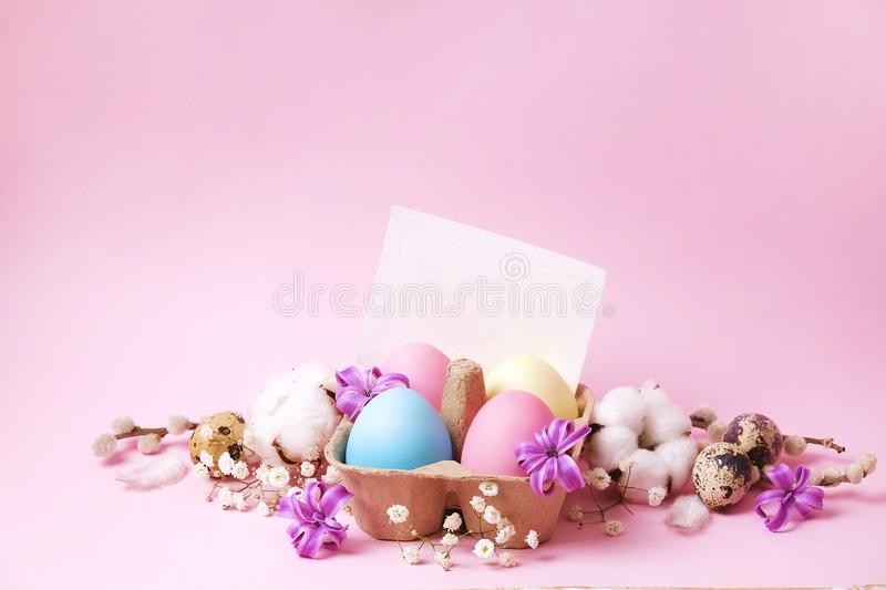 Traditional easter card template with pastel colors painted organic eggs in wicker basket with hay and decorative wildflowers. royalty free stock images