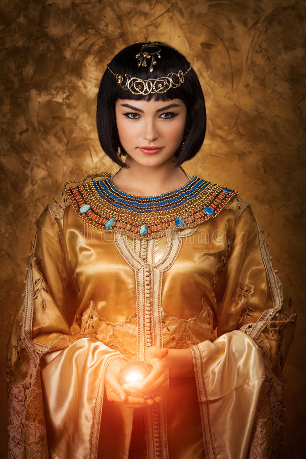 Beautiful Egyptian woman like Cleopatra with magic ball on golden background stock photo