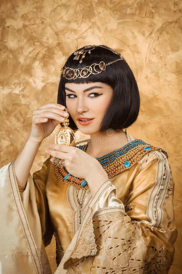 Beautiful Egyptian woman like Cleopatra with perfume bottle on golden background stock images