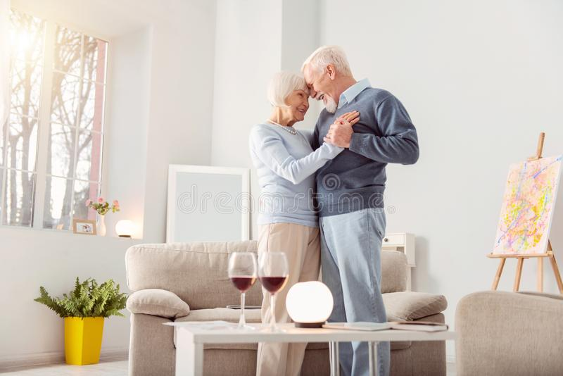 Beautiful elderly couple bonding while dancing. Deep in love. Pleasant elderly couple dancing waltz in the living room and leaning their foreheads against one royalty free stock photos