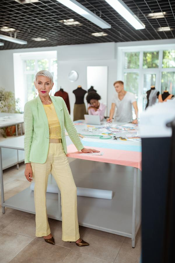 Beautiful elderly fashion designer standing in a workshop royalty free stock photography