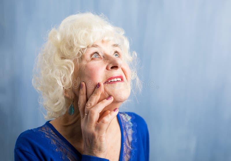 Beautiful elderly woman daydreaming royalty free stock image