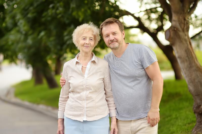 Beautiful eldery woman and her grown ups son together in park royalty free stock images
