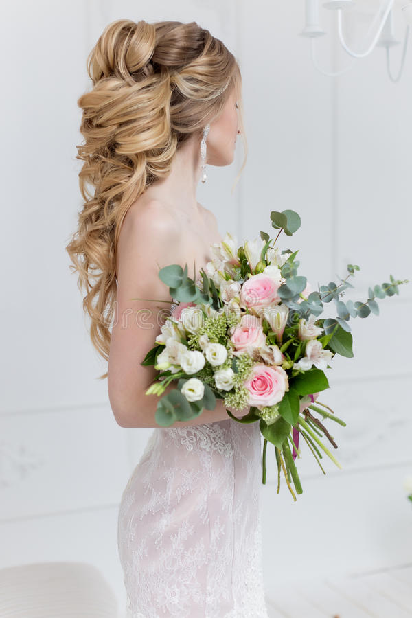 Beautiful elegant bouquet of roses and greenery in the gentle hands of the beautiful bride girl in a pink dress the air stock photos
