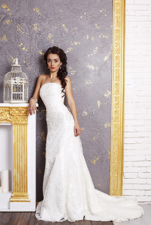 Beautiful elegant bride with dark hair posing at luxurious studio royalty free stock photography