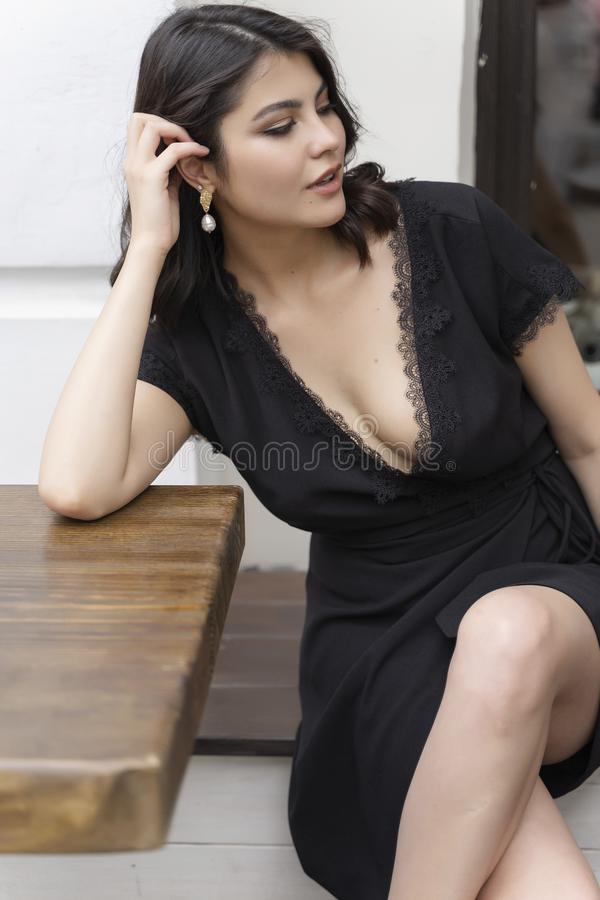 Beautiful elegant brunette girl wearing a black dress with a sexy deep neckline is relaxing in a street cafe. Advertising, fashion. Commercial design. Copy royalty free stock photos