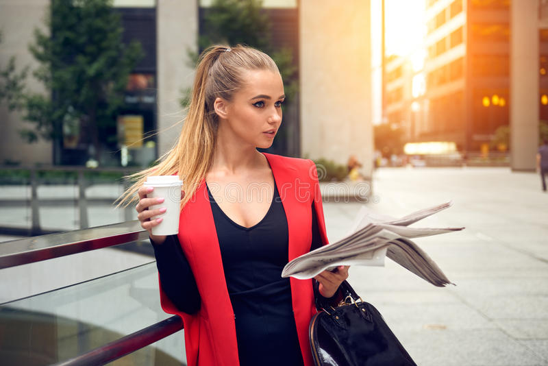 Beautiful elegant business woman walking to the city office with a coffee, newspaper and smiling outdoor stock photography