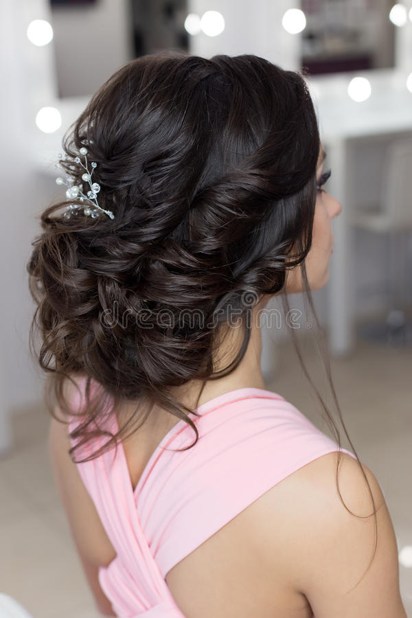 Beautiful elegant evening hairstyle on dark hair beautiful girl with an ornament from stones in her hair, hairstyle for the royalty free stock photos