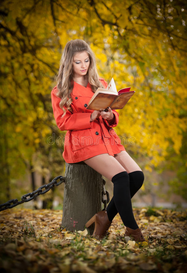 Beautiful elegant girl with orange coat reading sitting on a stump autumnal park. Young pretty woman with blonde hair reading. Beautiful elegant girl with orange royalty free stock images