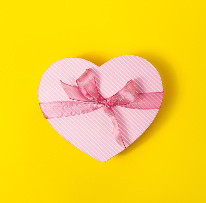 Beautiful elegant Present Gift in Heart Shape on Yellow colorful stock photography