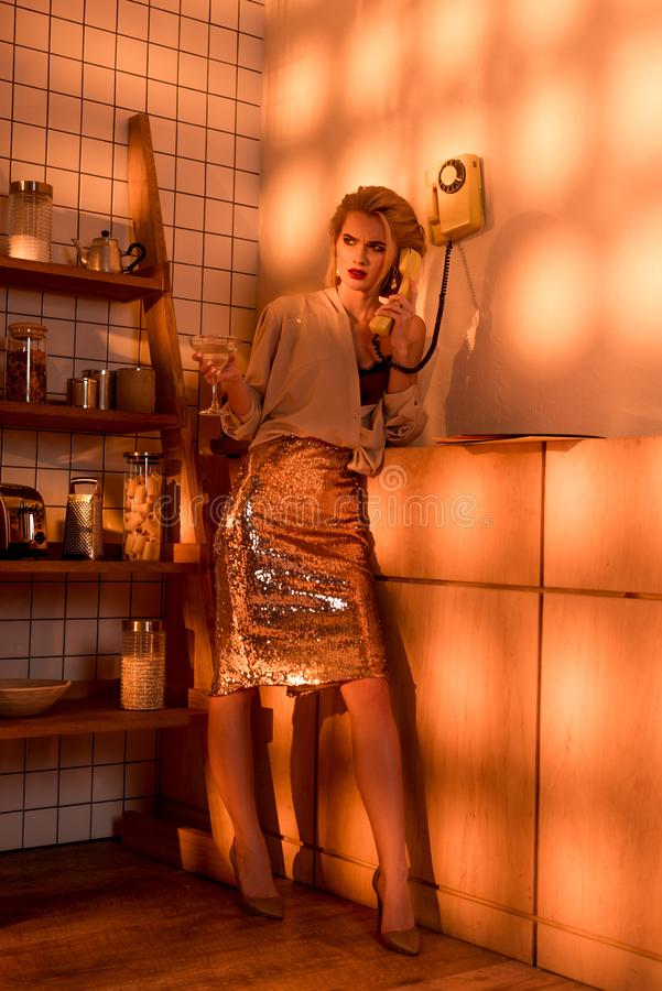Beautiful elegant woman with cocktail talking on retro telephone in kitchen. With orange light royalty free stock photography