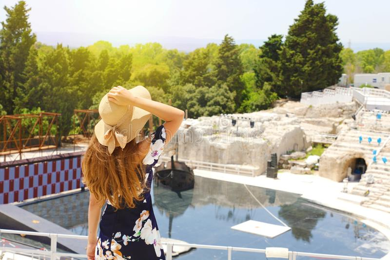 Beautiful elegant woman with hat and flowered dress in Syracuse Greek theater in Sicily, Italy, back view outdoors stock image