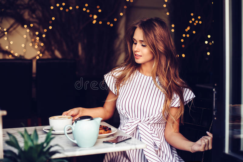 Beautiful elegant woman having breakfast drinking coffee and eating cake in city cafe stock image
