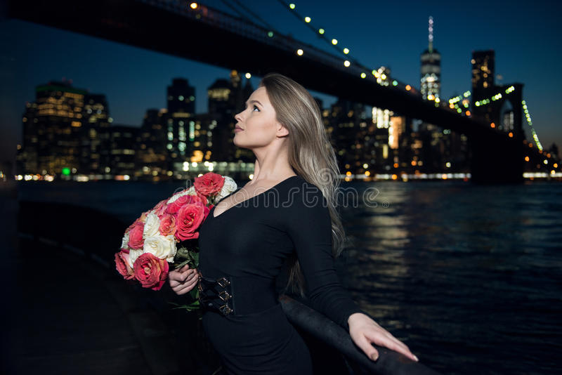 Beautiful elegant woman holding bouquet of rose flower wearing black evening dress in the city stock image