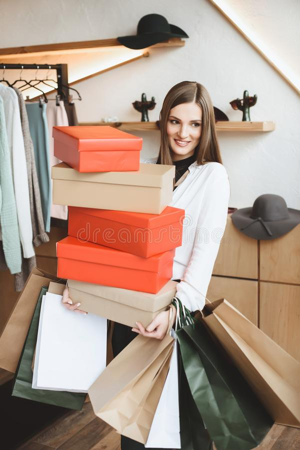 beautiful elegant woman holding shopping bags and shoe boxes royalty free stock images