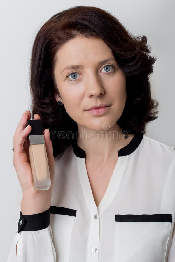 Beautiful elegant woman with make-up demonstrates the decorative cosmetic products in jars for applying makeup on a white backgrou royalty free stock photos