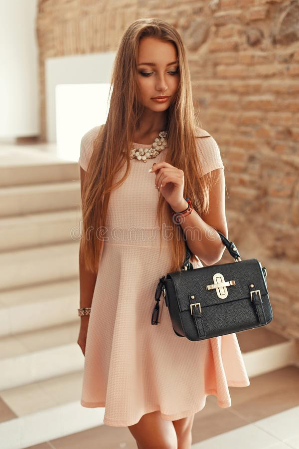 Beautiful elegant woman in a pink dress with a bag comes down royalty free stock photography