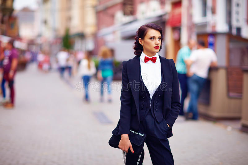 Beautiful elegant woman posing on crowded city street. Elegant woman posing on crowded city street royalty free stock image