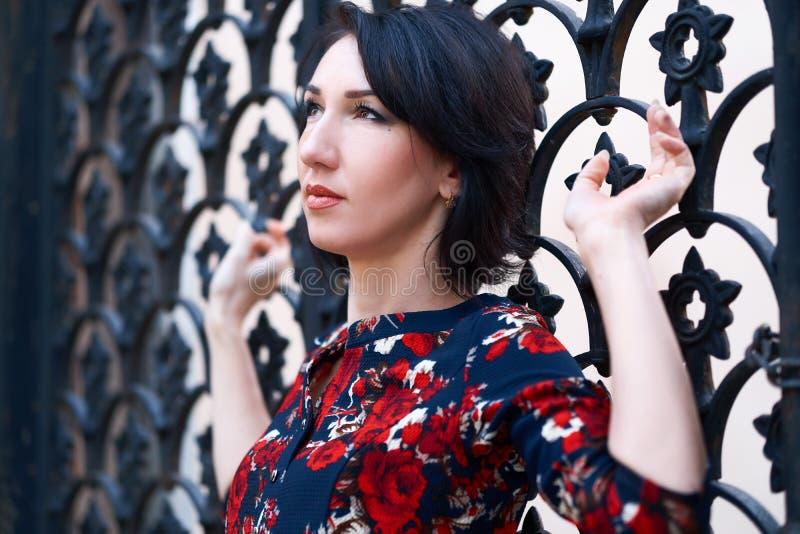 Beautiful elegant woman posing near black wrought iron gates stock images