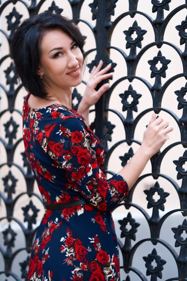 Beautiful elegant woman posing near black wrought iron gates royalty free stock photography